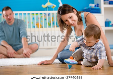 Portrait of happy family at home. Baby boy ( 1 year old ) and young parents father and mother sitting on floor and playing together at children's room, smiling.