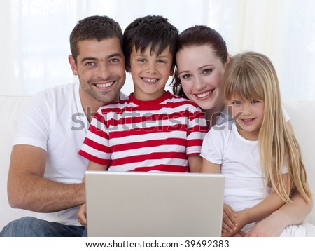 Portrait of happy family at home using a laptop