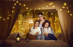 Portrait of happy family enjoying good quiet evening at home. Little kids and elder sister or young mother smiling at camera sitting in cosy bed tent decorated with lantern and yellow LED fairy lights