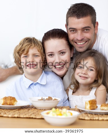 Portrait of happy family having breakfast in kitchen