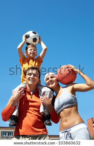 Portrait of happy family holding balls outside