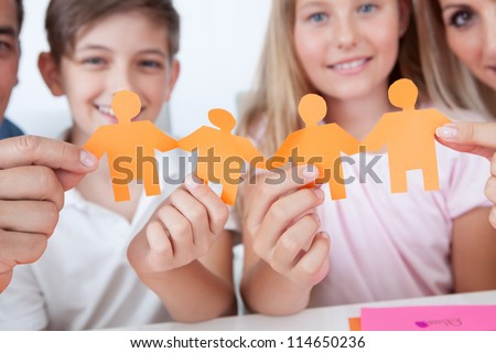 Portrait Of Happy Family Holding Paper People In Hand At Home