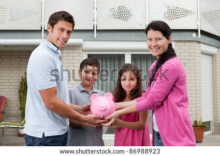Portrait of happy family holding piggy bank outside their house
