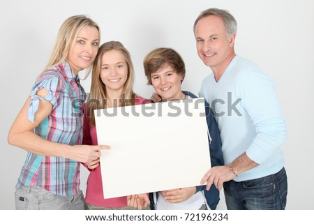 Portrait of happy family holding whiteboard