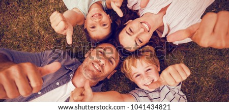 Portrait of happy family in park together gesturing thumbs up #1041434821