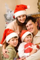 Portrait of happy family in Santa caps at home
