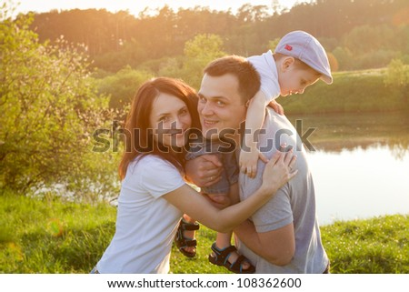 portrait of happy family in the park, mother, father and son