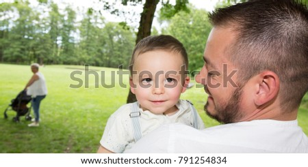 Portrait Of Happy Family In the summer park with mother in background with stroller #791254834