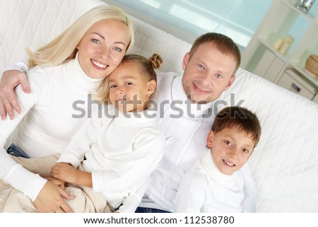 Portrait of happy family in white pullovers looking at camera at home