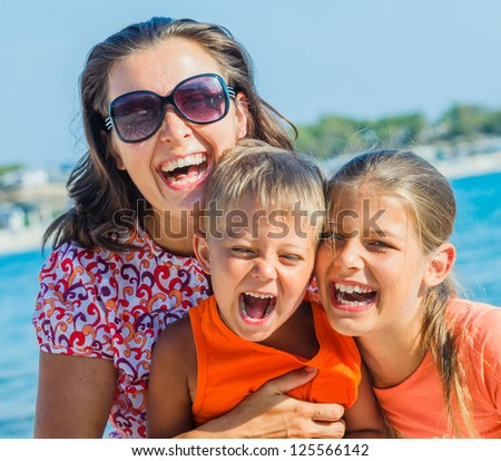 Portrait of happy family laughing and looking at camera on the beach