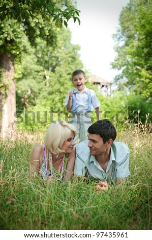 Portrait of happy family lying down on grass.
