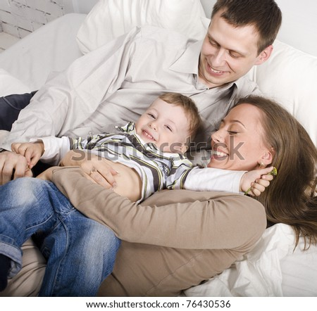 portrait of happy family, mom and dad playing with their son in bed