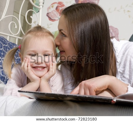portrait of happy family, mother and daughter in bed reading book and talking, laughing