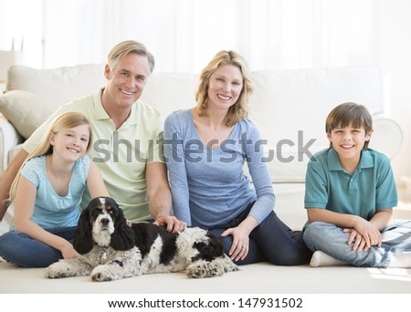 Portrait of happy family of four with pet dog sitting on floor in living room at home