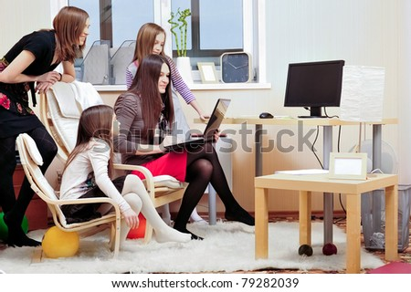 Portrait of happy family of only girls of different ages. They are looking at laptop display together