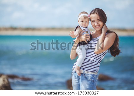 portrait of Happy Family of two mother and child having fun by the Sea shore