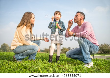 Portrait of happy family - Pretty young girl playing with soap bubbles in a park with her parents