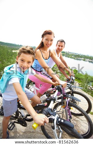 Portrait of happy family riding bikes in summer