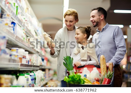 Portrait of happy family shopping in grocery store: choosing milk in dairy product department with cart full of food