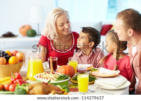 Portrait of happy family sitting at festive table and chatting - stock photo