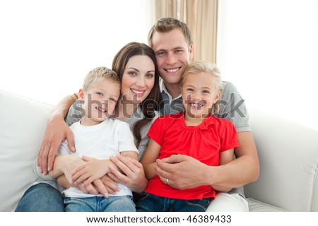 Portrait of Happy family sitting on sofa in the living room
