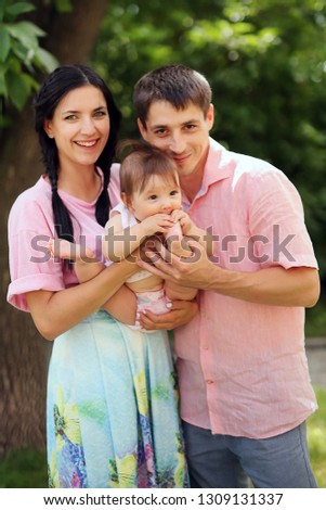 Portrait of happy family. Smiling parents holding their child. Handsome father and beautiful mother with little cute daughter having fun in the park. Pretty kid, pretty woman and man