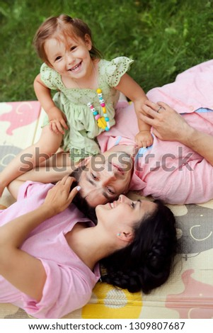 Portrait of happy family. Smiling parents  lie on the grass with their child. Handsome father and beautiful mother with little cute daughter having fun in the park. Pretty kid, pretty woman and man