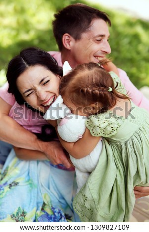 Portrait of happy family. Smiling parents with their child. Handsome father and beautiful mother with little cute daughter having fun in the park. Pretty kid, pretty woman and man
