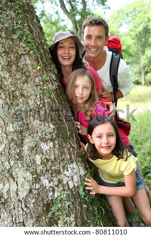 Portrait of happy family standing by a tree