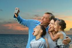 Portrait of happy family taking selfie on the sea beach