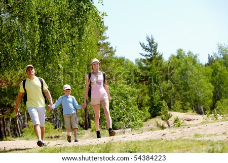 Portrait of happy family walking down countryside at summer