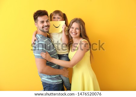 Portrait of happy family with drawn smile on sheet of paper against color background