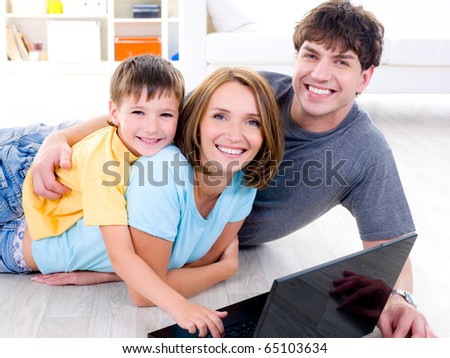 Portrait of happy family with litttle son on the floor with laptop - indoors