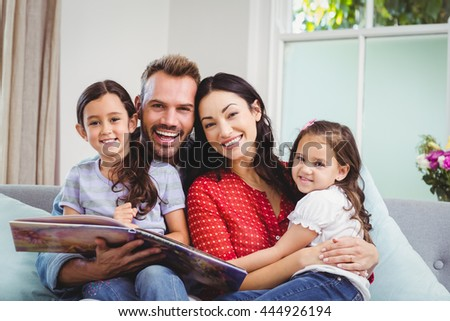 Portrait of happy family with picture book sitting on sofa at home