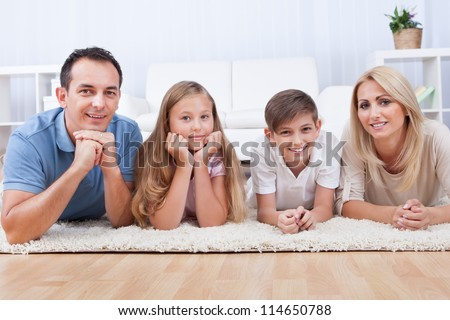 Portrait Of Happy Family With Two Children Laying On Carpet At Home
