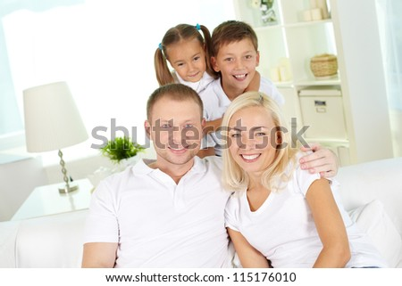 Portrait of happy family with two children looking at camera at home