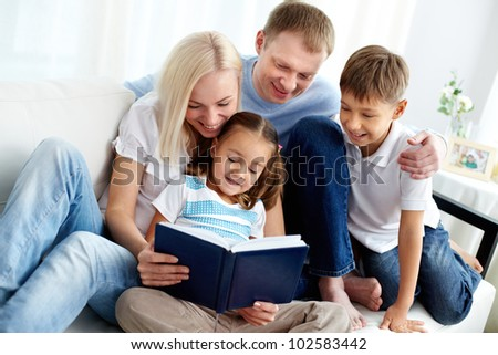 Portrait of happy family with two children reading book