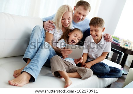 Portrait of happy family with two children sitting on sofa