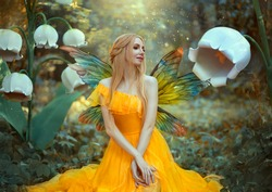 Portrait of happy fantasy woman blonde forest fairy. Fashion model in a bright yellow dress with butterfly wings sits posing in nature. Large flowers scenery decor white lilies. Light magic radiance