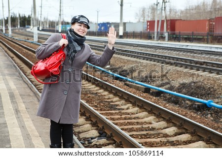 Portrait of happy fashion young Caucasian woman waving goodbye. Copy space