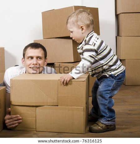 portrait of happy father and his son moving in new house