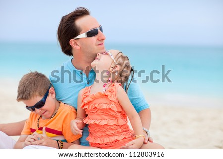 Portrait of happy father and kids enjoying beach vacation