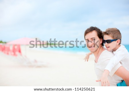 Portrait of happy father and son enjoying time at beach