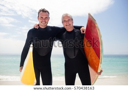 Portrait of happy father and son in wetsuit embracing on the beach on a sunny day
