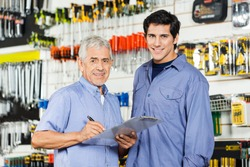 Portrait of happy father and son preparing checklist in hardware store