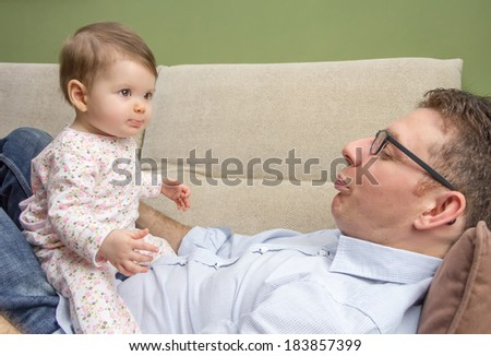 Portrait of happy father playing with cute baby sitting over his belly in a sofa at home