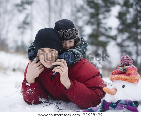 portrait of happy father with his son outside with snowman - stock photo