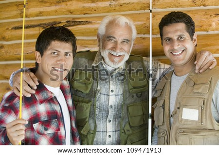 Portrait of happy father with two sons holding fishing rods