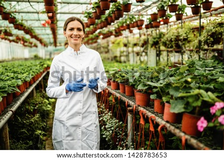 Portrait of happy female biologist standing in a plant nursery and looking at camera.  Photo stock ©