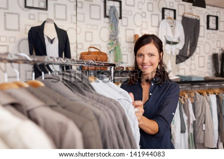Portrait of happy female customer choosing shirt in clothing store